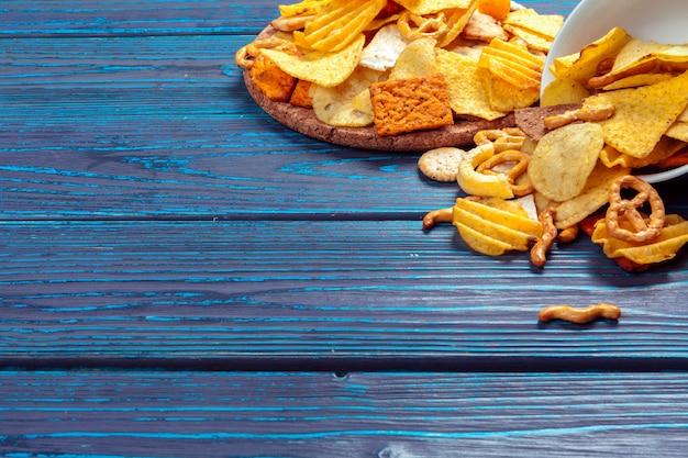 Verschiedene arten von junk-food, salzstangen, salz-cracker auf holztisch im stillleben