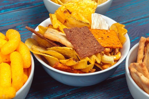 Verschiedene arten von junk-food, salzstangen, salzgebäck auf holzuntergrund