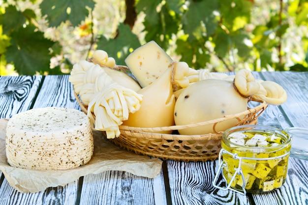 Verschiedene arten von käse auf einem hölzernen hintergrund vor dem hintergrund des grünen laubs.
