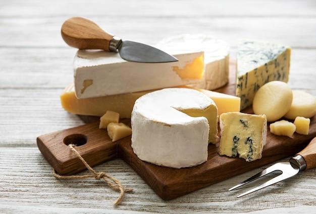 Verschiedene arten von käse auf einem weißen hölzernen hintergrund