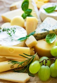Verschiedene arten von käse, basilikum und trauben auf einem tisch
