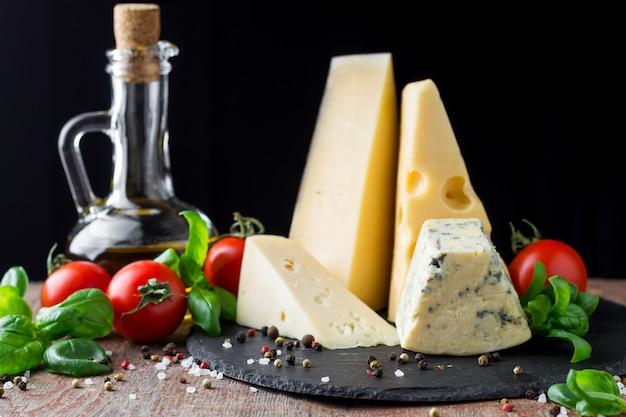 Verschiedene arten von käse, tomaten und olivenöl auf einem dunklen