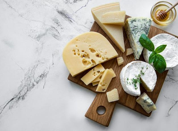 Verschiedene arten von käse, trauben und honig auf einem marmorhintergrund