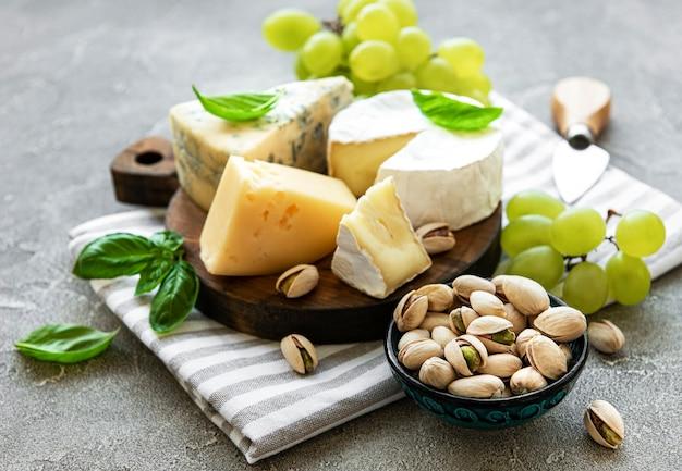 Verschiedene arten von käse, trauben und snacks auf grauem betonhintergrund