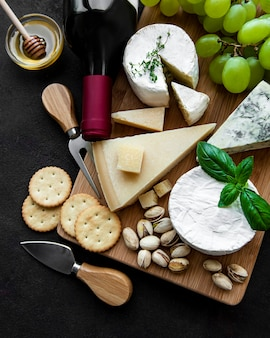 Verschiedene arten von käse, trauben und wein auf einem schwarzen betonhintergrund