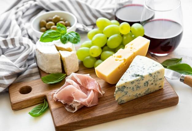 Verschiedene arten von käse, trauben, wein und snacks auf weißem marmorhintergrund Premium Fotos