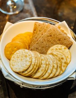Verschiedene arten von keksen mit vielen formen kreisen und quadratischen inneren weißen schüssel.