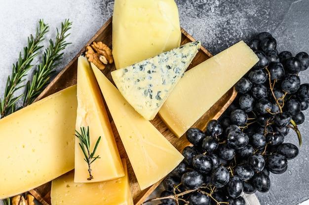 Verschiedene arten von leckerem käse mit walnüssen und trauben Premium Fotos