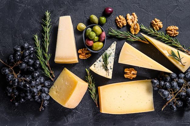 Verschiedene arten von leckerem käse, walnüssen und trauben. draufsicht