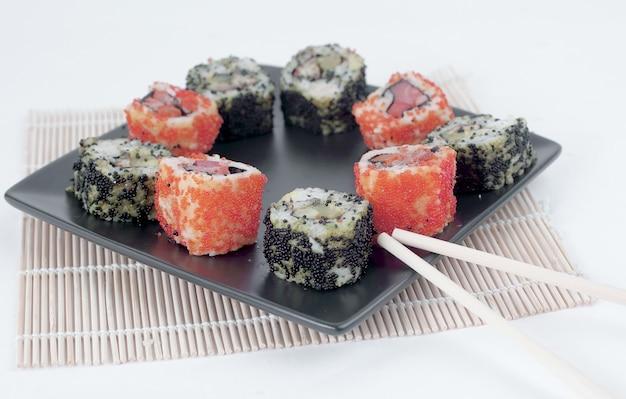 Verschiedene arten von maki-sushi und essstäbchen auf einem schwarzen teller