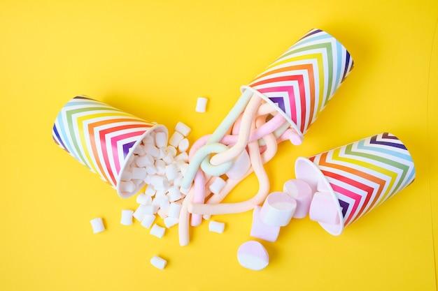 Verschiedene arten von marshmallows fallen aus festlichen pappbechern mit geometrischem muster auf gelbem hintergrund, kopierraum, draufsicht