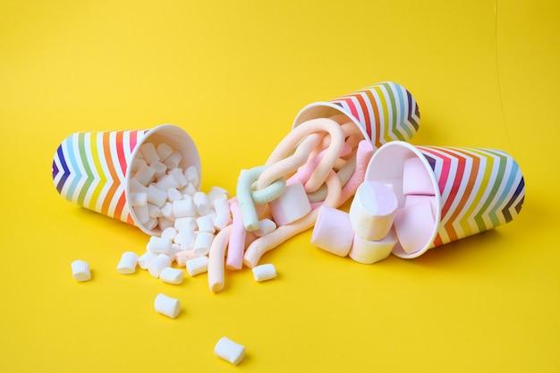 Verschiedene arten von marshmallows fallen aus festlichen pappbechern mit geometrischem muster auf gelbem hintergrund, kopierraum