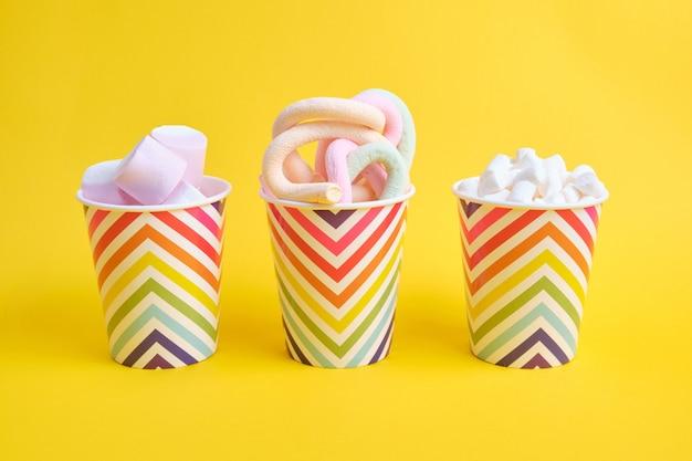 Verschiedene arten von marshmallows in festlichen pappbechern mit geometrischem muster auf gelbem hintergrund