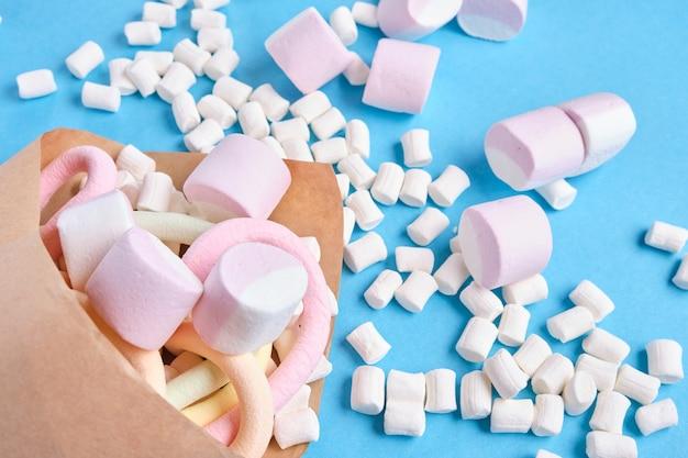 Verschiedene arten von marshmallows in papier eingewickelt auf blauem hintergrund