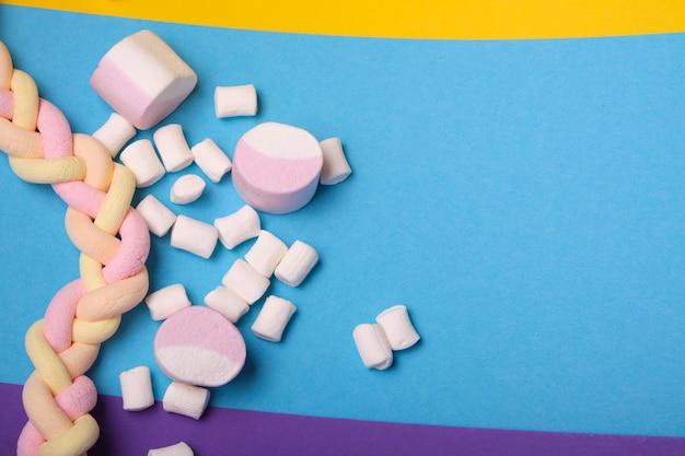 Verschiedene arten von marshmallows mit unterschiedlichen geschmacksrichtungen auf einem bunten hintergrund, lange spaghetti-förmige marshmallows sind zu einem zopf geflochten