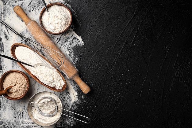 Verschiedene arten von mehl in holzschalen auf schwarzem tisch, draufsicht