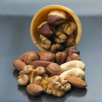 Verschiedene arten von nüssen in einem waffelkegel auf einem grauen tisch. gesundes und proteinreiches essen