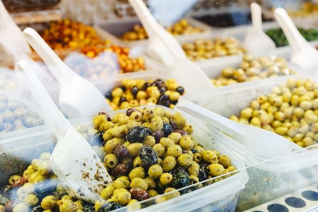 Verschiedene arten von oliven auf dem markt. mischen sie grüne, schwarze oliven mit knoblauch, pesto-sauce, kräutern auf einer theke mit einer kugel zum verkauf.