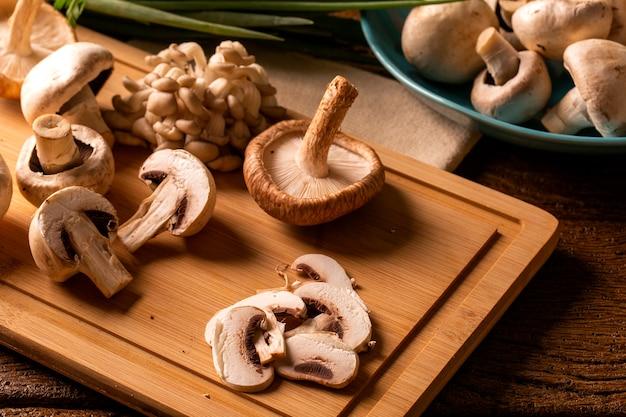 Verschiedene arten von pilzen auf einem holztisch.