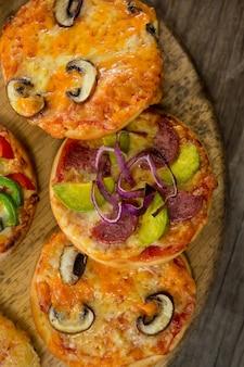 Verschiedene arten von pizza auf einem holztablett angeordnet