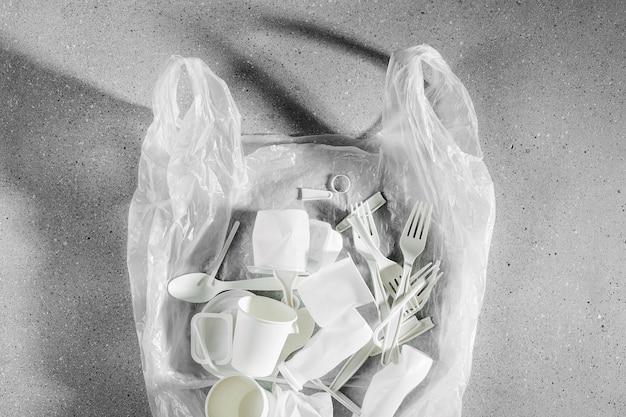 Verschiedene arten von plastikmüll in plastiktüten. lebensmittelverpackungen aus kunststoff auf hellem hintergrund. konzept des recyclings von kunststoff und ökologie. flache lage, ansicht von oben