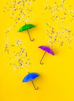 Verschiedene arten von reiskörnern, die auf drei spielzeugschirme auf leuchtendem gelbem tisch gießen. künstlerisches konzept des frühlingsregens