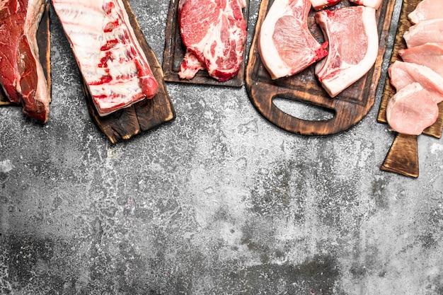 Verschiedene arten von rohem fleisch auf den brettern auf rustikalem tisch.
