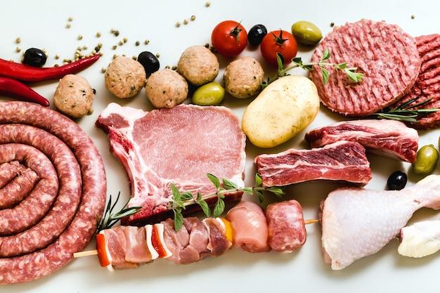 Verschiedene arten von rohem fleisch: hähnchenschenkel, burger mit schweinefleisch und rindfleisch, rippchen und kebabs, putenfleischbällchen, fertig zum kochen mit kartoffeln, paprika, oliven und schwarzen oliven sowie aromatischen kräutern