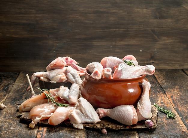 Verschiedene arten von rohem hühnerfleisch mit kräutern in einer schüssel auf holztisch.