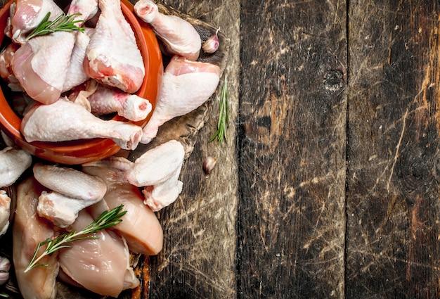 Verschiedene arten von rohem hühnerfleisch mit kräutern in einer schüssel.