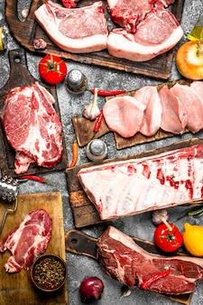 Verschiedene arten von rohem schweinefleisch und rindfleisch mit gewürzen und kräutern.