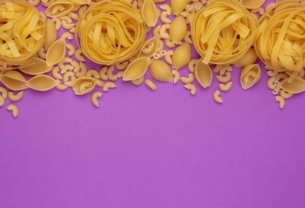 Verschiedene arten von rohen italienischen nudeln auf lila hintergrund. draufsicht. speicherplatz kopieren
