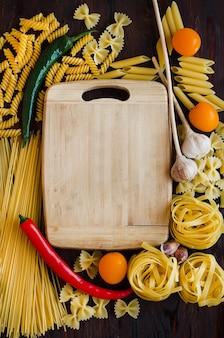 Verschiedene arten von rohen nudeln. kochrezept mit gemüse.