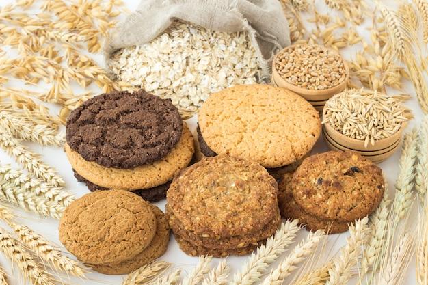 Verschiedene arten von runden keksen, haferflocken in einer tüte, weizen und hafer in holzkisten. spikes von weizen und hafer auf einem weißen tisch