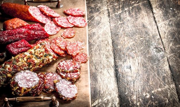 Verschiedene arten von salami auf den brettern auf einem hölzernen hintergrund