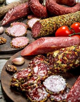 Verschiedene arten von salami auf einem brett mit nüssen auf einem rustikalen tisch.