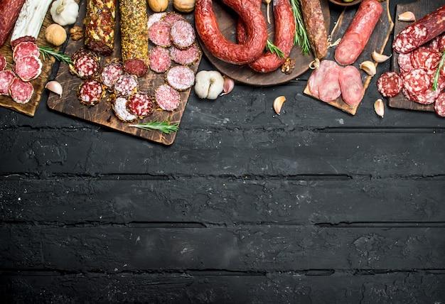Verschiedene arten von salami auf holzbrett auf schwarzem rustikalem tisch.
