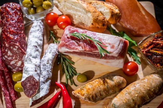 Verschiedene arten von salami, speck und würstchen auf einem holztisch