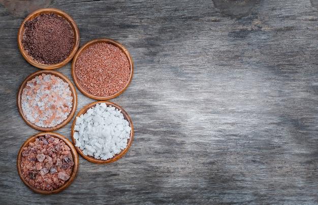 Verschiedene arten von salz auf einem holztisch. himalaya, hawaiianer, wein, tafel, meersalz