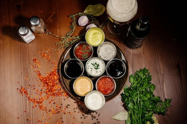 Verschiedene arten von saucen und ölen in schalen, draufsicht