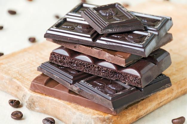 Verschiedene arten von schokoladenstücken ragen mit kaffeebohnen hoch
