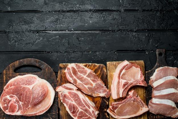 Verschiedene arten von schweinefleisch. auf einem schwarzen rustikalen.