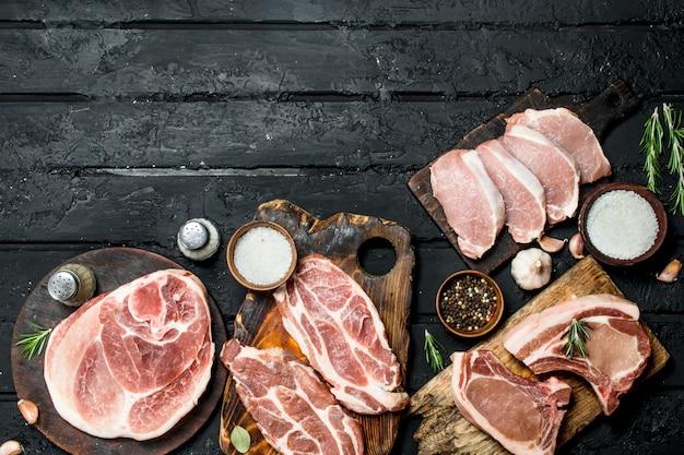 Verschiedene arten von schweinefleisch mit gewürzen auf einem schwarzen rustikalen tisch.