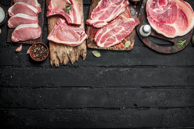 Verschiedene arten von schweinefleisch mit gewürzen. auf einem schwarzen rustikalen.