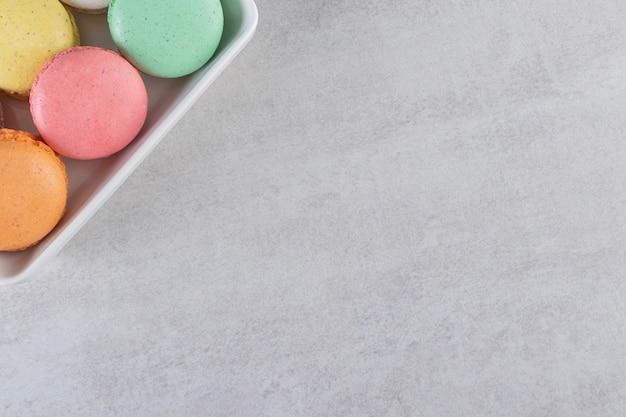 Verschiedene arten von süßen mandelkuchen in weißer schüssel auf steinoberfläche