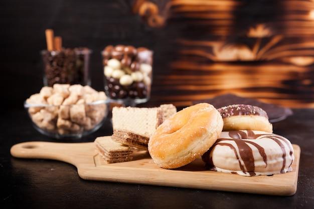 Verschiedene arten von süßigkeiten auf holzbrett und hintergrund