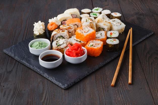 Verschiedene arten von sushi-essen auf schwarzem stein serviert