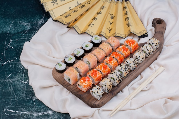 Verschiedene arten von sushi-rollen auf holzplatte mit stäbchen und japanischem fächer serviert.