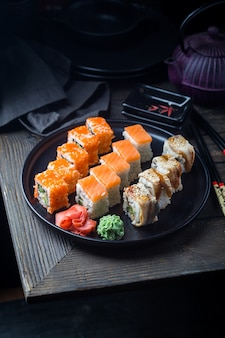 Verschiedene arten von sushi-rollen werden auf einem schwarzen teller über der dunkelheit serviert