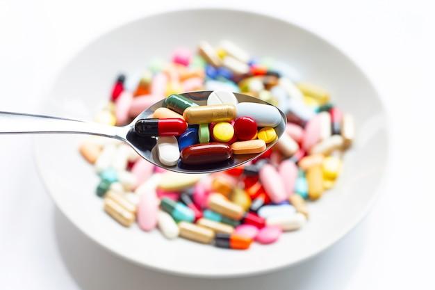 Verschiedene arten von tabletten, kapseln und pillen auf löffel mit buntem medizinhintergrund.